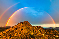 Full rainbow around a mountain peak st sunrise