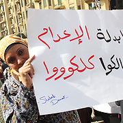 """In Cairo's Tahrir Square, a woman bearing the sign, """"All of you, congratulations for the death penalty"""" peers out from behind it."""