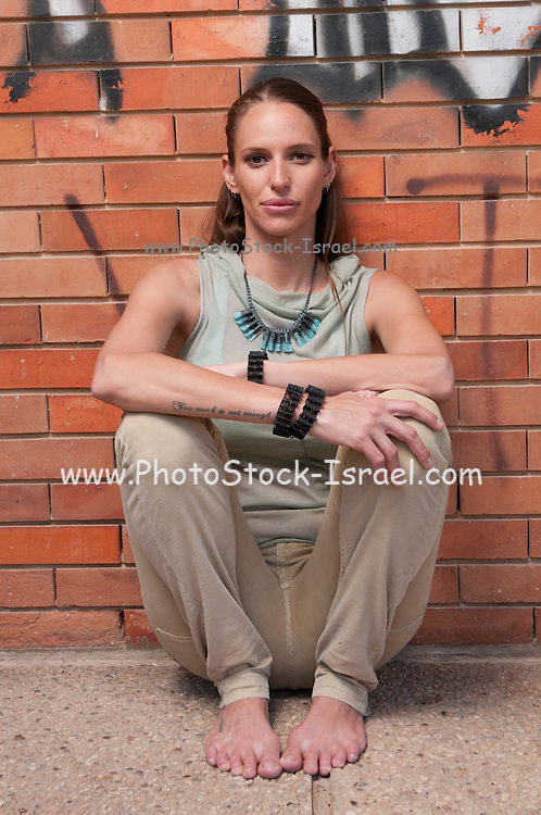 A hip and trendy sulking young woman stands in front of a brick wall with graffiti Model release available