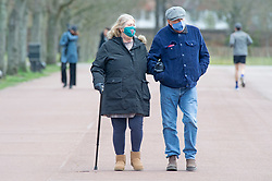 © Licensed to London News Pictures 08/04/2021. Greenwich, UK. A couple out walking in the park wearing protective masks. People out and about in Greenwich Park, London as coronavirus lockdown restrictions continue to ease in the UK. Photo credit:Grant Falvey/LNP