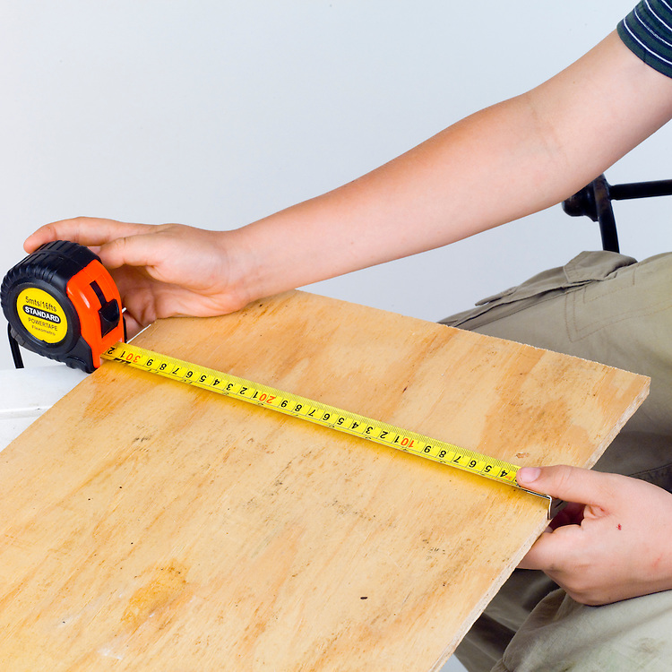 A boy using a measurement tape to measure the width of a piece of wood.