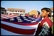 African-American girl & her eighth-grade class hold 30-foot by 42-foot garrison flag to raise up at Fort McHenry; Baltimore. Maryland