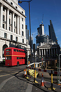 Red Routemaster bus passes roadworks in the City of London, England, United Kingdom.