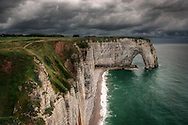 """A moody representation, with an incoming storm in the background, of the cliff known as La Manneporte, which is part of the amazing rocky coast around Etretat in Upper Normandy, France, altogether known as Les Failases d'Etretat..La Manneporte, which in French means """"the great door"""" is one of the most beloved subject of the famous French impressionist painter Claude Monet, who depicted it in more of 40 paints..Monet loved very much Etretat and its cliffs, and settled here his house and atelier for years.."""