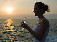 woman caucasian driking water by the seaside with sunset sunrise