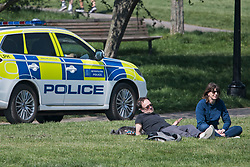 © Licensed to London News Pictures. 10/04/2020. London, UK. A Police patrol car drives past two people sun bathing on Primrose Hill in London, during a pandemic outbreak of the Coronavirus COVID-19 disease. The public have been told they can only leave their homes when absolutely essential, in an attempt to fight the spread of coronavirus COVID-19 disease. Photo credit: Ben Cawthra/LNP