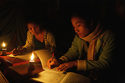 Derlow and Chanda are students that live in the Dorm close to Ponglath Secondary school.  They live in simple grass huts which will soon be replaced by concrete built dormitories with kitchens and good toilets, funded by the EU.  They have to work at night to keep up with their studies although they have no electricity and use torches and oil lamps. Pha Oudom District, Bokeo Province, Lao PDR