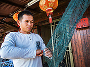 15 NOVEMBER 2016 - GEORGE TOWN, PENANG, MALAYSIA:  A man repairs his fishing nets on the Chew Jetty, one of the traditional Chinese clan jetties in George Town, Penang. George Town is a UNESCO World Heritage city and wrestles with maintaining its traditional lifestyle and mass tourism.           PHOTO BY JACK KURTZ