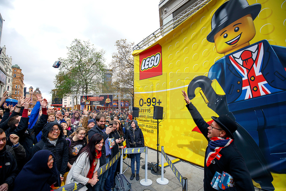 © Licensed to London News Pictures. 17/11/2016. London, UK. Lego fans try to catch a freebie whilst queuing for the world's largest Lego Store to be opened in Leicester Square, London on 17 November 2016. Photo credit: Tolga Akmen/LNP