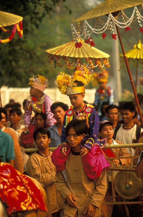 Attendants dance with boys dressed up as princes on their shoulders at Poy Sang Long, the yearly ordination of novice monks, Mae Hong Son, Thailand.