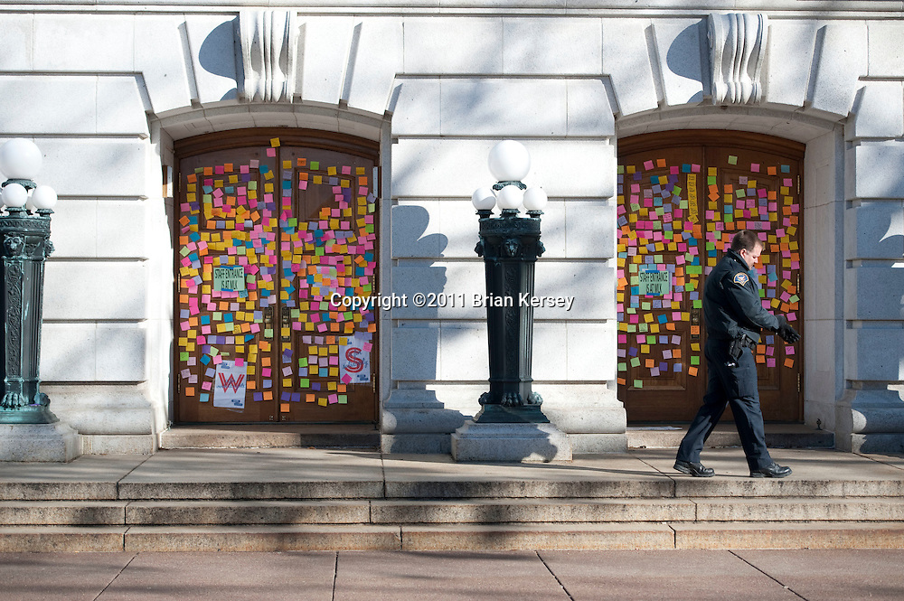 A police officer stands watch at a set of doors covered in notes supporting protesters and condemning Wisconsin Gov. Scott Walker at the state Capitol on March 2, 2011 in Madison, Wisconsin. Protests over a budget restructuring bill slashing benefits and eliminating most collective bargaining rights for state employees entered their third week as about 100 protesters remained camped-out inside the Capitol.     (Photo by Brian Kersey)