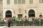 Spectators,many wearing green, line Fifth Avenue in front of the jeweller Van Cleef & Arpels.