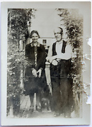 adult elderly couple standing with dog in garden gate opening 1900s
