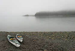 Kayaker's kayaks beached on a foggy Sebree Island beach await pickup by the daily tour boat, Baranof Wind. View is looking west from Sebree Island to Tlingit Point in Glacier Bay National Park and Preserve in southeast Alaska.