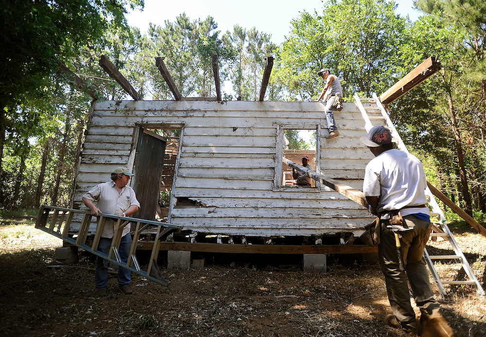 Project site contractor Kerry Shackelford, left, carries a ladder while supervising his crew as they dismantle an 18th-century slave cabin piece by piece, Monday, May 13, 2013, in Edisto Island, South Carolina before it is shipped to the Smithsonian's new National Museum of African American History and Culture in Washington, D.C. (Stephen Morton for The New York Times)