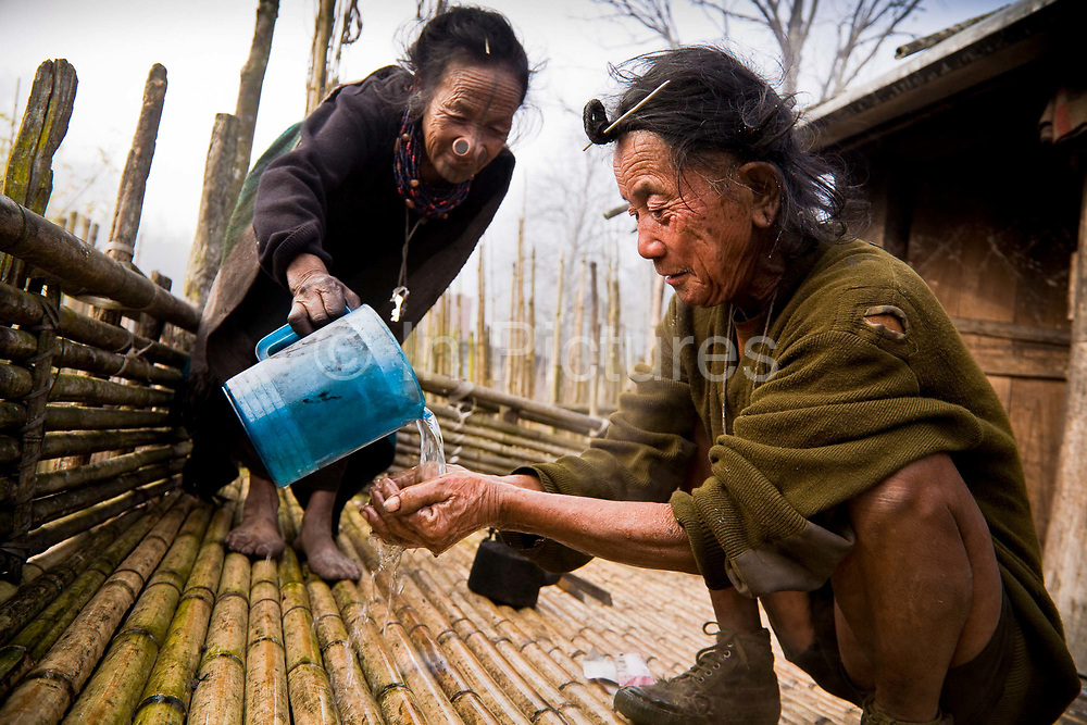 "Apatani tribal elders Atta Yadd and her husband Ba Khang wake up in the early morning, freshen up on the raised bamboo platform of  their one roomed ""open plan"" bamboo made stilted hut, sleeping on mats in the center close to the bamboo fire which is protected by a brick-lined hearth in the village of Hijja, Arunachal Pradesh. The Apatani tribe are one of hundreds of indigenous tribes scattered across India, particularly the north east. Their origins are from Mongolian nomadic tribes whom settled on the Ziro plateau, close to the Chinese border, they practice fixed agriculture as well as forestry, planting trees on the rim of the plateau as well as bamboo forests from which they derive fire wood, building their homes as well as using the bamboo for all manner of applications in their daily lives, cooking utensils and household containers amongst other uses. They carefully cultivate bamboo forests allowing them to grow, but not flower and die, as this would spell disaster for their very own existence. They also tend to their rice fields and live stock for what is mostly a subsistence economy. The Indian constitution recognizes over 500 indigenous tribes, which account for 8.5% of the total population"