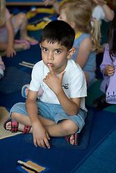 Nursery school boy sitting on a rug listening to a story,