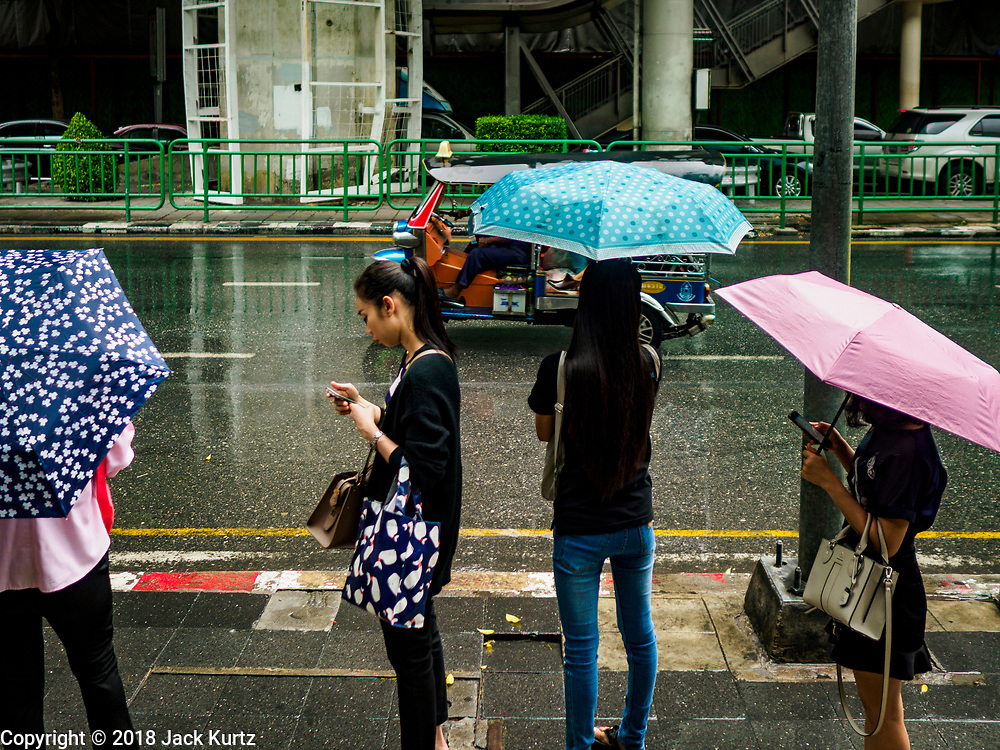 19 JULY 2018 - BANGKOK, THAILAND: People on Silom Road under umbrellas during a monsoon rain in Bangkok.     PHOTO BY JACK KURTZ