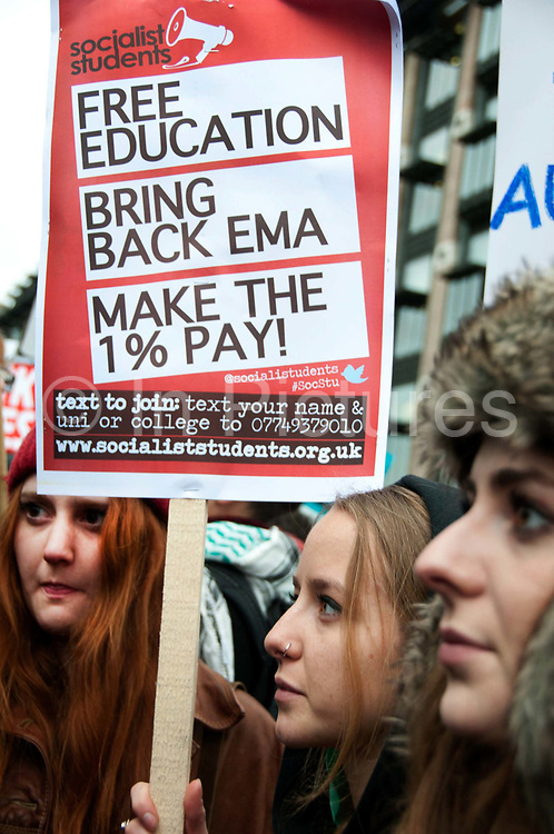 November 21st. Westminster. Demonstration organised by National Union of Students (NUS) against education cuts. Young female students hold a placard saying 'Free education. Bring back EMA. Make the 1% pay'.