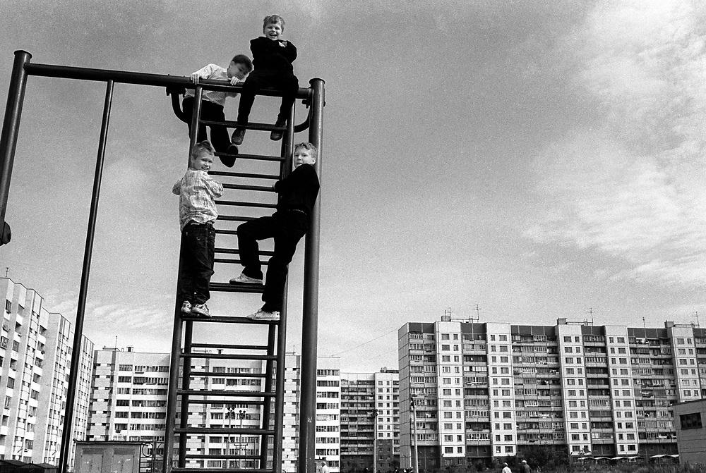 Children playing on climbing frame near block of flats<br /> St Petersburg, Russia 1994