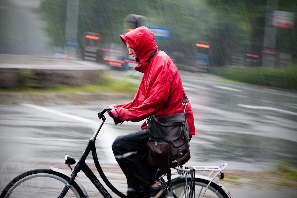 Een fietser rijdt ingepakt in een regenpak door het centrum van Utrecht. De regen komt met bakken uit de lucht.<br /> <br /> A cyclist is riding in the rain.