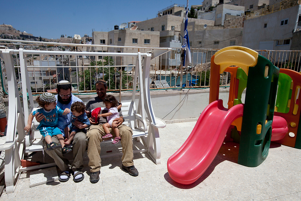 Jewish settlers and their chilren sit at the rooftop of their home, named Beit Yonatan in the east Jerusalem neighborhood of Silwan, during a visit by the Israeli parliament committee for the children's rights to houses of Jewish families residing in a mostly Palestinian area, July 6, 2010.
