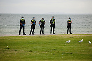 Police watch protesters from the sand on St Kilda Beach foreshore during the Sack Daniel Andrews Protest that stared in Fawkner Park. Parts of the community are looking to hold the Victorian Premier accountable for the failings of his government that led to more than 800 deaths during the Coronavirus crisis. Victoria has recorded 36 days Covid free as pressure mounts on the Premier Daniel Andrews to relax all remaining restrictions. (Photo by Michael Currie/Speed Media)
