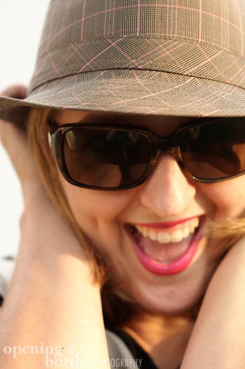 A woman wearing a fedora, Kate Spade sunglasses and pink lipstick strikes a flirty pose.