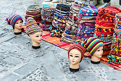 Mannequin heads on ground wearing colorful hats in marketplace, Chefchaouen, Morocco