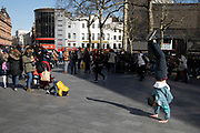 Young boy tries to mimick a street performer in Leicester Square who is performing a hand stand in London, England, United Kingdom.