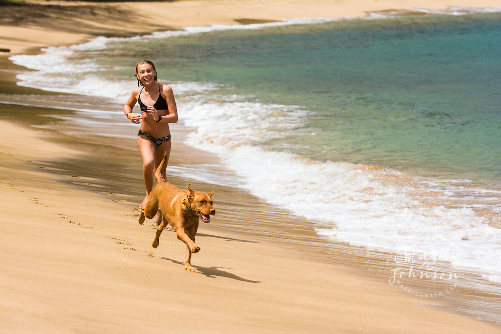 10 year old girl playing at the beach with her dog, Hanalei, Kauai, Hawaii people *****Property Release available ****Model Release available
