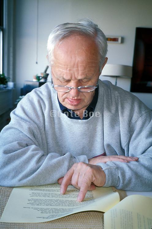 An elderly man wearing glasses reading