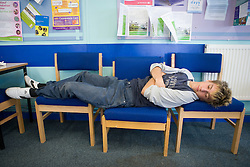 Teenage boy; taking a break; lying on chairs in the school common room,