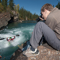 Photographer Alec Ptlowany shoots pictures of kayaker Peter Thompson paddling through rapids in the Kananaskis River near Calgary, Alberta, Canada.
