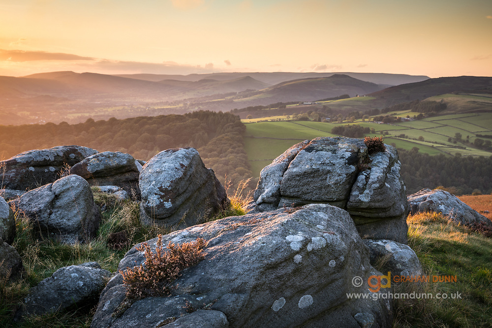 Wonderfully warm and soft evening light on Carhead Rocks in the Peak District. Win Hill, Lose Hill, Mam Tor and the Hope Valley look on in the distance. A sunset landscape scene in Derbyshire, England, UK.
