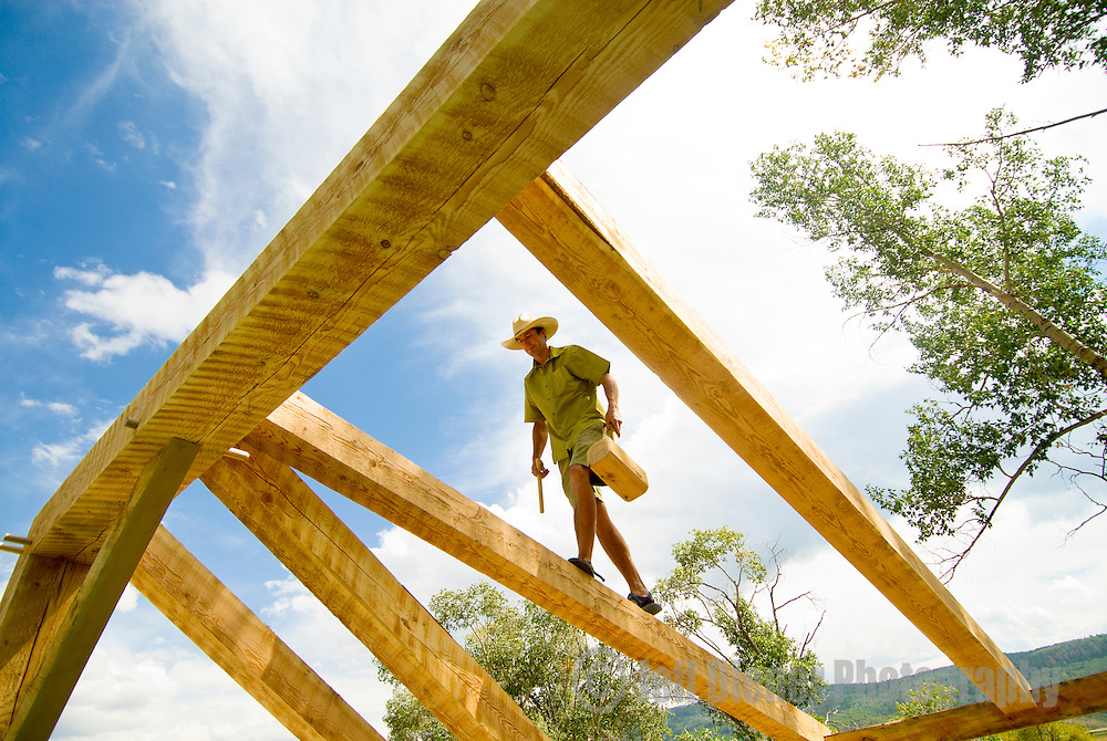 A young man walks a rafter during construction of a Timber Frame house in Teton Valley, Idaho.
