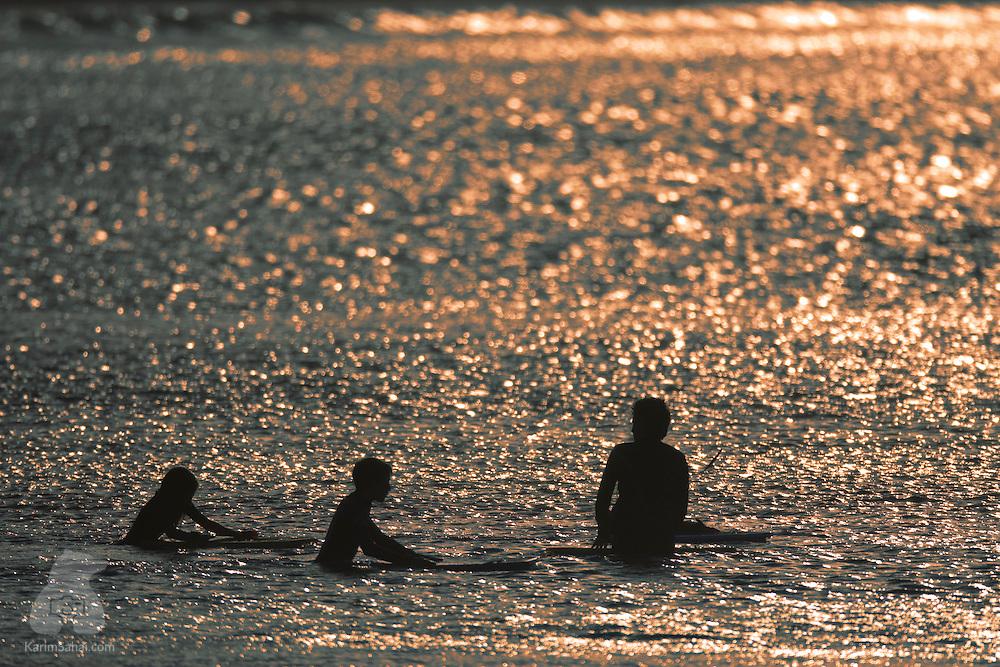 Three surfers on a calm sea at dusk, Lyall Bay, Wellington, New Zealand.
