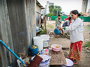 05 SEPTEMBER 2013 - BANGKOK, THAILAND:  A Cambodian woman washes her dishes after her shift at the construction site of a new high rise apartment / condominium building on Soi 22 Sukhumvit Rd in Bangkok. The workers live in the corrugated metal dorms on the site. Most of the workers at the site are Cambodian immigrants.             PHOTO BY JACK KURTZ