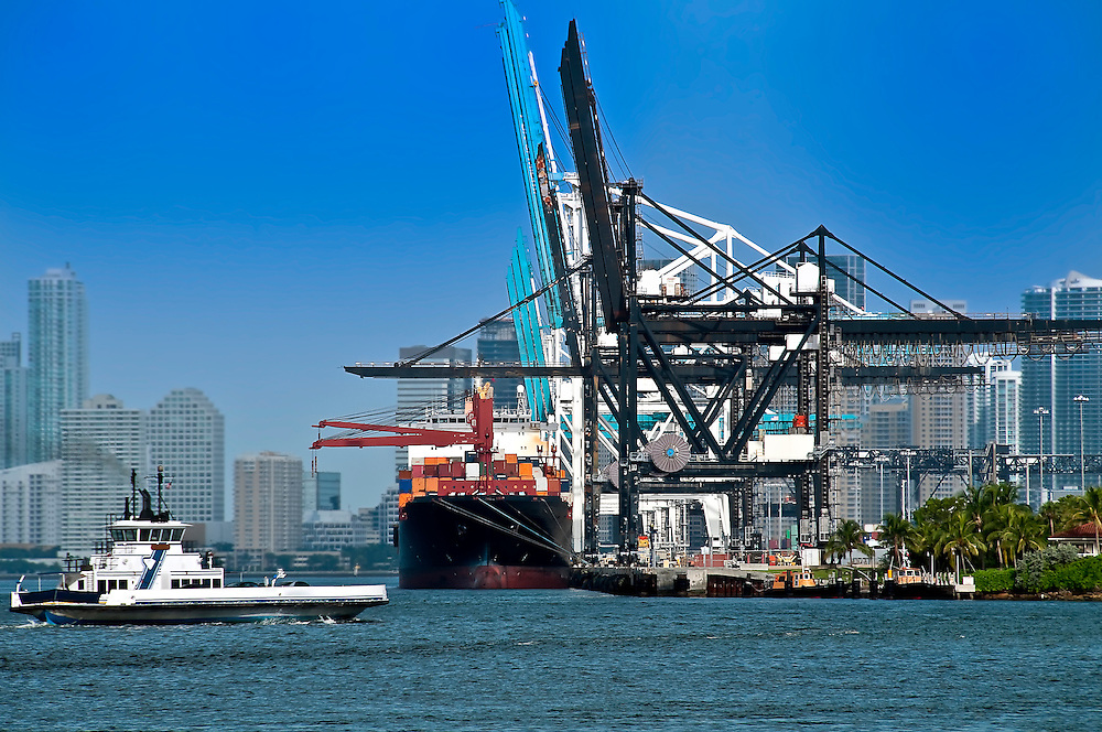 View of ferry boat and cargo ship in the Miami Seaport with the city in the background.