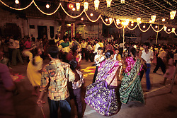 India, Rajasthan, Udaipur. Young Garba dancers clack partners' sticks and move to next dancer; Laxmi festival