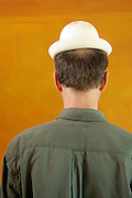 start balding male person with a to small white plaster bowler style  hat