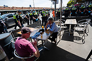 Locals drinking beer are surrounded by police and protesters  during an Extinction Rebellion protest in Melbourne.  A small group of climate protesters marched from Flagstaff Gardens to The Queen Victoria Market and ending with two individuals gluing themselves together, and then glued themselves to Victoria Avenue outside of the Market. This comes as 5 new COVID-19 cases were uncovered in Melbourne's revamped Hotel Quarantine, breaking almost 40 days of virus free days. (Photo by Dave Hewison/Speed Media)