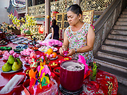 25 AUGUST 2018 - GEORGE TOWN, PENANG, MALAYSIA: A woman at Leong San Tong Khoo Kongsi Temple sets out the banquet for the spirits on Ghost Day, the full moon day (or night) that falls in the middle of Hungry Ghost month. The Ghost Festival, also known as the Hungry Ghost Festival is a traditional Taoist and Buddhist festival held in Chinese communities throughout Asia. Ghost Day, is on the 15th night of the seventh month (25 August in 2018). During Ghost Festival, the deceased are believed to visit the living. In many Chinese communities, there are Chinese operas and puppet shows and elaborate banquets are staged to appease the ghosts.       PHOTO BY JACK KURTZ