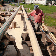 The Schooner Ardelle being built by Harold Burham, a member of the 11th generation of his family to build wooden boats in Essex, MA. Here a craftsman is shaping one of the two masts.