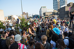 London, UK. 20th April 2019. Large numbers of police officers stand around climate change campaigners from Extinction Rebellion on Waterloo bridge as part of an operation to try to clear the bridge of the activists and visitors. The bridge has now been blocked throughout the six days of the International Rebellion called by Extinction Rebellion to demand urgent action to combat climate change by the British government.