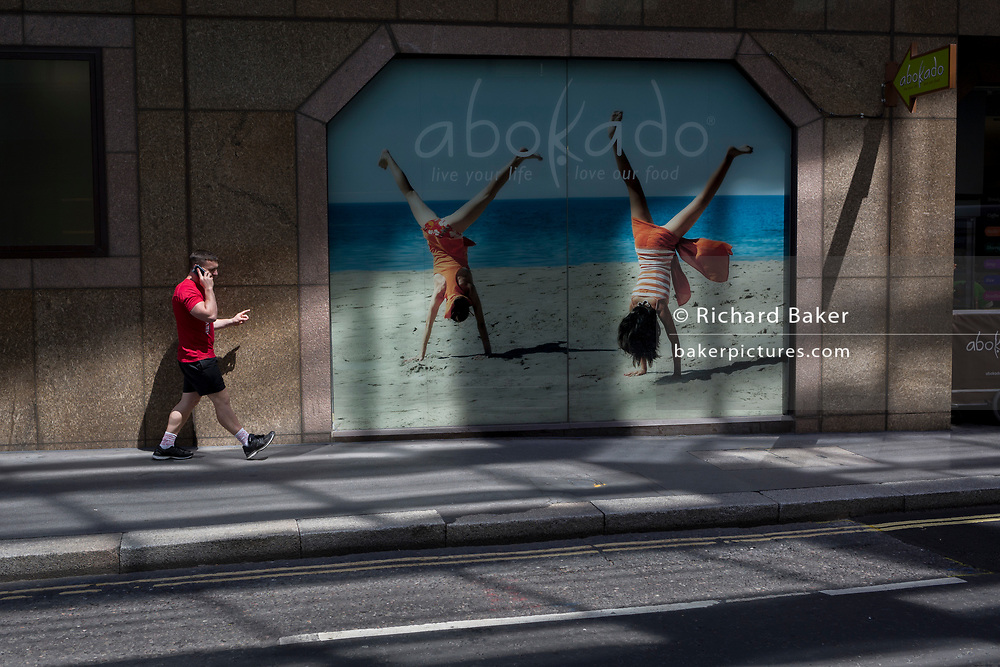 A pedestrian using a smartphone walks past a business window of healthfood and coffee retailer Abokado, on 26th June, in the City of London, England. Abokado is a fast food chain based in the United Kingdom, founded by Mark Lilley and his wife Lindsay in 2004, with the first store opening in London's Covent Garden.