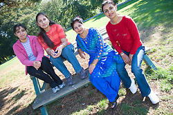 Four friends sitting on a park bench together,