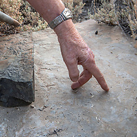 An archaeologist investiigates a grinding stone at an early Native American settlement in the White Mountains of California.  Tiny scratches show where stone blades were used to chop something.