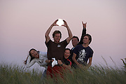 A rowdy bunch of friends crowd around as one reaches hands up to encircle the rising full moon - Middletown, RI 2007