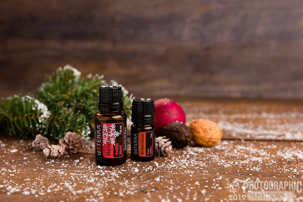 Holiday setting for essential oils, complete with fake snow and pine needles.